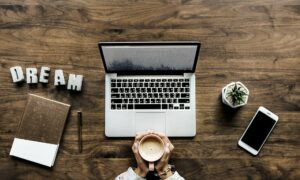 Na biurku jest laptop, na którym jest robiona strona na Wordpress, telefon, długopis, notesik i ręce Pani która trzyma kawę